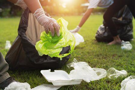 two people keeping garbage plastic bottle into black bag at park in morning light Stok Fotoğraf - 130720918