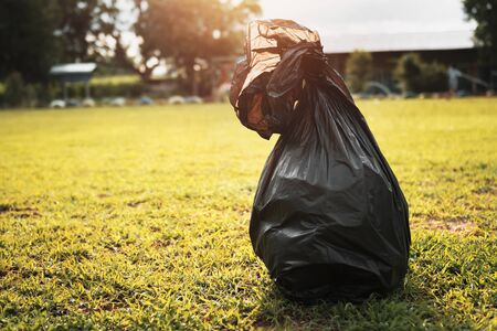 garbage black bag on grass with sunlight background Stok Fotoğraf - 130721038