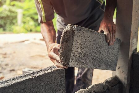 hand of worker plastering cement on brick wall at construction site