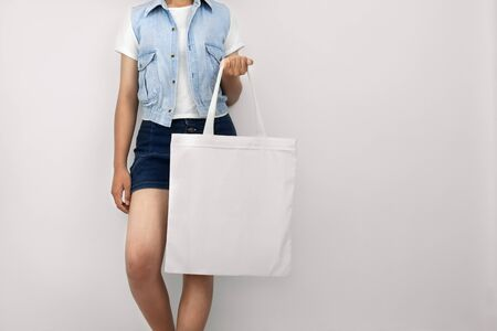 young woman holding eco cotton bag on wall white background Stok Fotoğraf