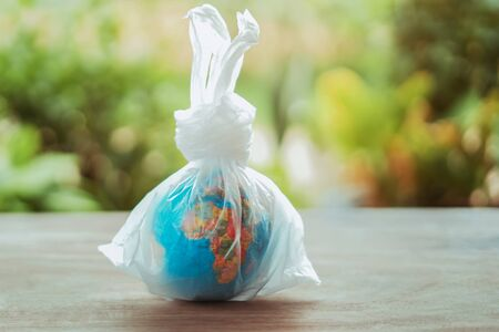 earth day concept globe in plastic bag on table Stok Fotoğraf