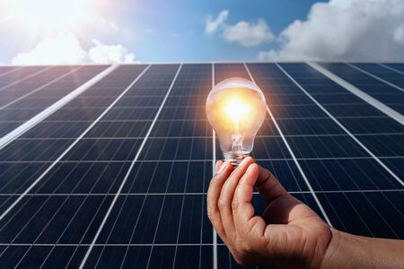 hand holding lightbulb on solar panel concept clean energy in nature Stok Fotoğraf