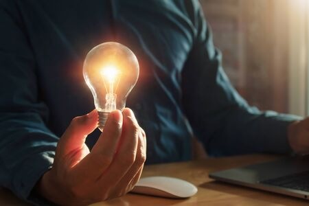 concept saving energy with innovation and inspiration. businessman holding lightbulb in office