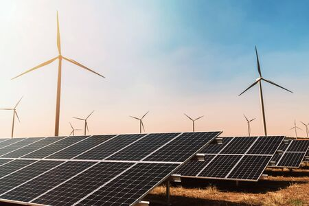 Konzept für saubere Energie. Sonnenkollektor mit Windkraftanlage und blauem Himmel