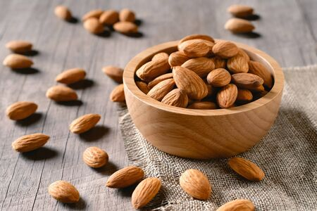 almonds in bowl wood on dark table background