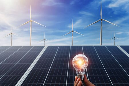 hand holding lightbulb with solar panel and wind turbine background. clean energy in nature concept