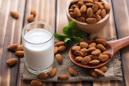 almonds in bowl wood with spoon and milk on dark table background