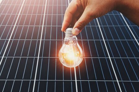 hand holding lightbulb with solar panel background. clean energy in nature concept