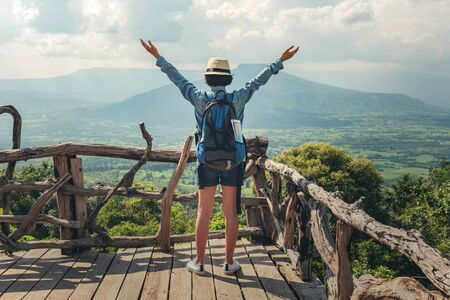 Woman traveler with backpack enjoying view and happy freedom at mountains