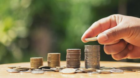 saving money hand putting coins on stack on table with sunshine. concept finance and accounting Imagens - 132068972