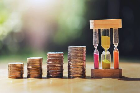 money stack with hourglass on table  and sunset