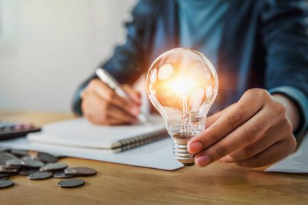 concept save energy power. businesswoman holding light bulb