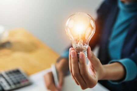 concept save energy power. businesswoman holding light bulb in office Stock fotó