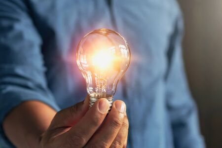 businessman hand holding lightbulb. idea Alternative energy concept saving electricity