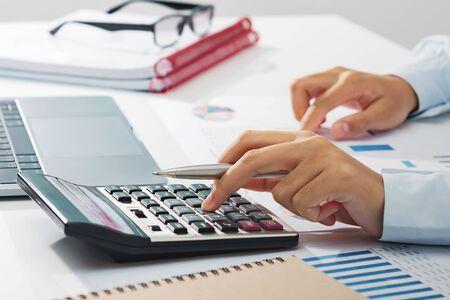 zakenvrouw die aan het bureau werkt met behulp van een rekenmachine die financiële boekhouding op kantoor analyseert