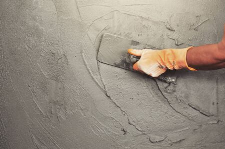 hand of worker plastering cement at wall for building house