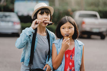 two girl eating ice cream on street during walking travel at park Imagens