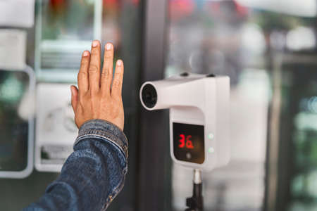 close up hand checking temperature before entering to shop by an automatic infrared