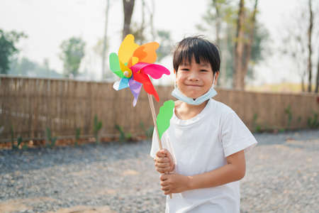 A boy holding a toy windmill happily walking in the park and wearing a mask to protect against the virus Standard-Bild