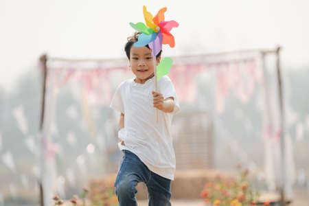boy holding a toy windmill happily runing in the park