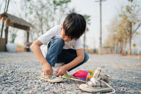 boy sitting in a park with shoelaces