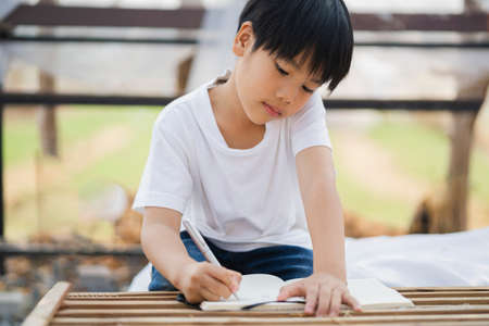 children boy writing on paper for doing homework at school