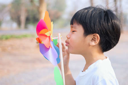 boy blowing a toy windmill in the morning at the park