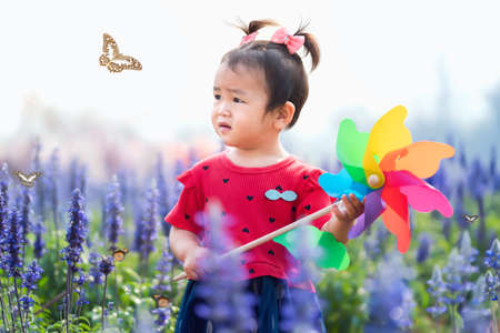 children girl standing in flower garden and holding toy windmill looking at butterfly Standard-Bild