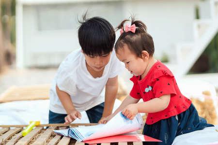 two children open book reading for learning Standard-Bild