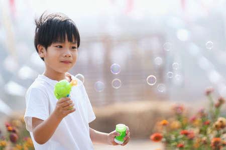 asian boy blowing soap bubbles Standard-Bild