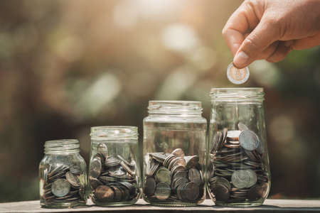 Idea saving money hand putting coins in to jug glass. finance accounting concept