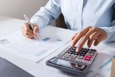 Woman accountant use calculator and computer with holding pen on desk in office. finance and accounting concept