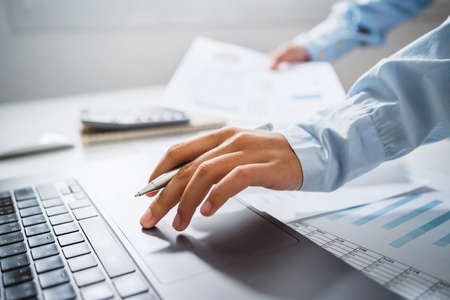 Business woman working in finance and accounting Analyze financial budget in the office Standard-Bild