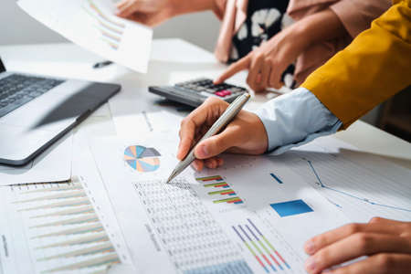 close up hand accountant holding pen pointing on paperwork chart for meeting team in office room. concept finance and accounting