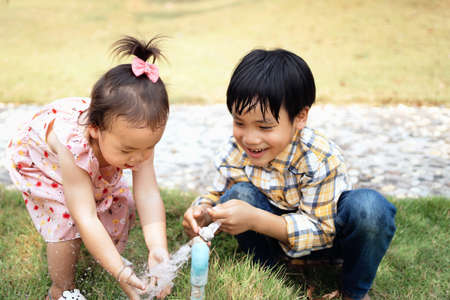 Two brothers and sisters play water from the tap