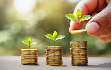 saving money hand putting coins on stack with small tree growing. concept finance and accounting