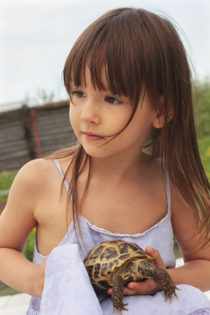 Pretty little girl holding a russian tortoise