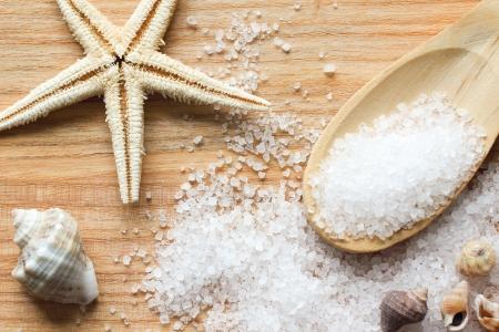 Zeezout kristallen in een houten lepel met zee schelpen en zeesterren op houten achtergrond