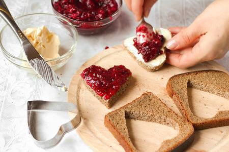 petit déjeuner: Femme cuisson un petit-déjeuner sucré - pain avec de la confiture Banque d'images