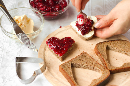 love making: Woman cooking a sweet breakfast - bread with jam Stock Photo