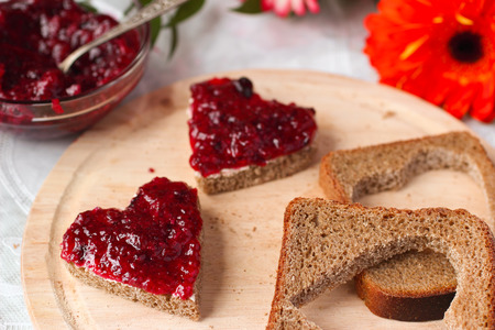 hand jam: Sweet hearts made of bread with butter and blackberry jam