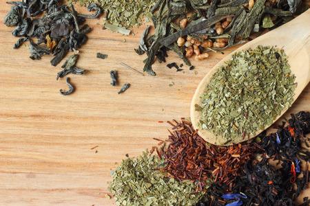 yerba mate: Té de yerba seca en una cuchara sobre fondo de madera con la colección de té
