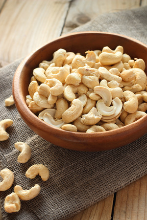 Raw cashew nuts in wooden bowl on rustic table 版權商用圖片