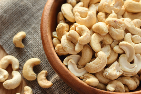 Raw cashews close-up in wooden bowl on sackcloth