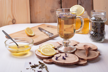 Traditional Russian drink with honey, lemon and dried herbs in a glass cup on wooden table Stockfoto