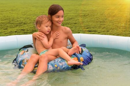 Happy loving sister and small brother in a inflatable pool in summer outdoors. Summer vacation and relax concept Archivio Fotografico