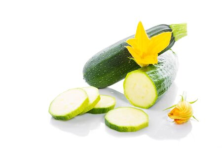 Zucchini or green marrow squash with green leaves and flowers isolated on white background