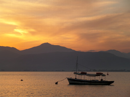 nafplio: A Boat Floating on the Aegean Sea under Beautiful Golden Sky After Sunset , Nafplio, Greece Stock Photo