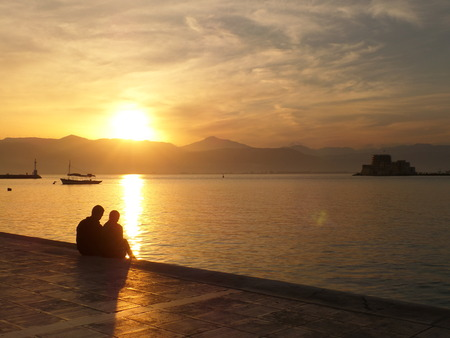 nafplio: Lovers watching a Romantic Sunset at the Promenade of  Nafplio, Greece