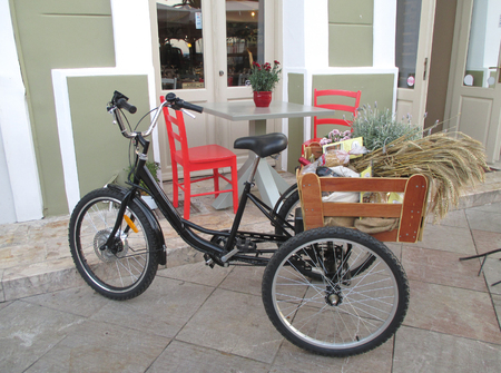 nafplio: A Black Bike and Two Red Chairs of a Charming Cafe in a town of Nafplio, Greece